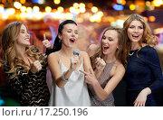 Купить «happy young women with microphone singing karaoke», фото № 17250196, снято 21 ноября 2015 г. (c) Syda Productions / Фотобанк Лори