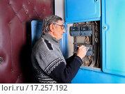 Купить «Пожилой мужчина переписывает показания счетчика за электроэнергию возле квартиры в подъезде», эксклюзивное фото № 17257192, снято 24 декабря 2015 г. (c) Яна Королёва / Фотобанк Лори