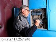Купить «Пенсионер переписывает показания счетчика за электроэнергию в подъезде дома», эксклюзивное фото № 17257240, снято 24 декабря 2015 г. (c) Яна Королёва / Фотобанк Лори