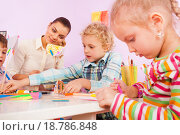 Купить «Воспитатель в детском саду помогает детям мастерить поделки из бумаги», фото № 18786848, снято 28 ноября 2015 г. (c) Сергей Новиков / Фотобанк Лори