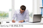 Купить «busy businessman with laptop and papers in office», видеоролик № 18956516, снято 9 июля 2015 г. (c) Syda Productions / Фотобанк Лори