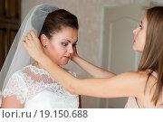 Купить «Подружка помогает одеть фату невесте», эксклюзивное фото № 19150688, снято 13 сентября 2015 г. (c) Игорь Низов / Фотобанк Лори