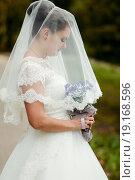 Купить «Портрет невесты накрытой фатой с цветами в руках», эксклюзивное фото № 19168596, снято 13 сентября 2015 г. (c) Игорь Низов / Фотобанк Лори
