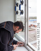 Купить «Снятие фиксаторов стеклопакета пластикового окна для извлечения оконного блока», эксклюзивное фото № 19557216, снято 25 декабря 2015 г. (c) Вячеслав Палес / Фотобанк Лори