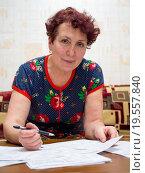 Пожилая проверяет правильность начисления платы за коммунальные услуги. Стоковое фото, фотограф Вячеслав Палес / Фотобанк Лори