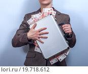 Женщина прижимает к груди чемодан, наполненный деньгами, на сером фоне. Стоковое фото, фотограф Pavel Biryukov / Фотобанк Лори