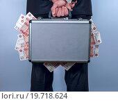 Купить «Мужчина держит за спиной чемодан, наполненный деньгами, на сером фоне», фото № 19718624, снято 9 января 2016 г. (c) Pavel Biryukov / Фотобанк Лори