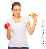 Купить «Young girl with apple and hamburger isolated», фото № 19917268, снято 25 июня 2019 г. (c) easy Fotostock / Фотобанк Лори