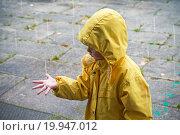Купить «Маленький ребенок в желтом плаще ловит ладонью капли дождя», фото № 19947012, снято 21 сентября 2015 г. (c) EugeneSergeev / Фотобанк Лори