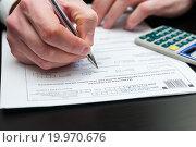 Купить «Заполнение налоговой декларации мужчиной», эксклюзивное фото № 19970676, снято 10 января 2016 г. (c) Игорь Низов / Фотобанк Лори