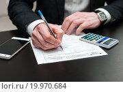Бизнесмен заполняет налоговую декларацию за столом. Стоковое фото, фотограф Игорь Низов / Фотобанк Лори
