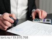 Купить «Мужчина ставит печать на документе», эксклюзивное фото № 19970768, снято 10 января 2016 г. (c) Игорь Низов / Фотобанк Лори