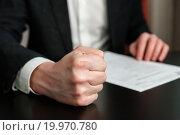 Купить «Бизнесмен стучит по столу кулаком на фоне деловых бумаг», эксклюзивное фото № 19970780, снято 10 января 2016 г. (c) Игорь Низов / Фотобанк Лори