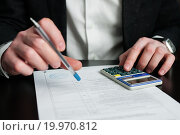 Купить «Бизнесмен с калькулятором сидит над документом», эксклюзивное фото № 19970812, снято 10 января 2016 г. (c) Игорь Низов / Фотобанк Лори