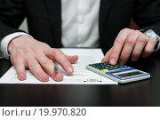 Купить «Мужчина рассчитывает на калькуляторе сумму налога», эксклюзивное фото № 19970820, снято 10 января 2016 г. (c) Игорь Низов / Фотобанк Лори