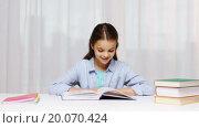 Купить «happy school girl reading book or textbook at home», видеоролик № 20070424, снято 12 декабря 2015 г. (c) Syda Productions / Фотобанк Лори