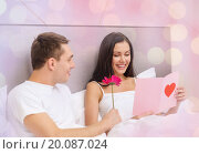 happy couple in bed with postcard and flower. Стоковое фото, фотограф Syda Productions / Фотобанк Лори