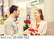 Купить «happy couple with present and flowers in mall», фото № 20089532, снято 10 ноября 2014 г. (c) Syda Productions / Фотобанк Лори