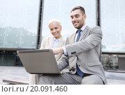 Купить «smiling businesspeople with laptop outdoors», фото № 20091460, снято 19 августа 2014 г. (c) Syda Productions / Фотобанк Лори