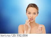 Купить «young woman applying lip balm to her lips», фото № 20192004, снято 31 октября 2015 г. (c) Syda Productions / Фотобанк Лори