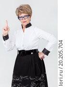 Строгая женщина среднего возраста поднимает указательный палец вверх. Стоковое фото, фотограф Кекяляйнен Андрей / Фотобанк Лори