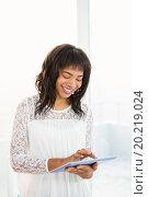 Купить «Smiling woman using her tablet in living room», фото № 20219024, снято 30 июня 2015 г. (c) Wavebreak Media / Фотобанк Лори