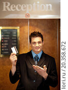 Купить «Snap shot of handsome guy holding cash card and showing it to camera», фото № 20358672, снято 5 июля 2012 г. (c) easy Fotostock / Фотобанк Лори