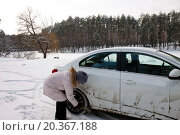 Женщина сметает грязь с машины. Стоковое фото, фотограф Левончук Юрий / Фотобанк Лори