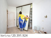 Купить «Worker setting mirrored doors on corner sliding wardrobe in room», фото № 20391924, снято 22 апреля 2014 г. (c) Losevsky Pavel / Фотобанк Лори