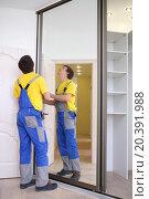 Купить «Young man fixing mirrored doors on corner sliding wardrobe in room», фото № 20391988, снято 23 апреля 2014 г. (c) Losevsky Pavel / Фотобанк Лори