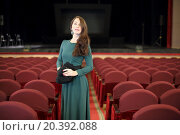 Купить «Beautiful young woman with dark long hair in a green evening dress standing in an empty auditorium with red seats», фото № 20392088, снято 12 марта 2014 г. (c) Losevsky Pavel / Фотобанк Лори