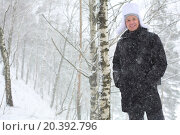 Купить «Portrait of smiling young man standing under snowfall in birch forest», фото № 20392796, снято 19 марта 2014 г. (c) Losevsky Pavel / Фотобанк Лори