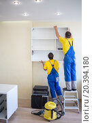 Купить «two male furniture adjusters in uniform hang wall drawer», фото № 20394180, снято 9 июля 2014 г. (c) Losevsky Pavel / Фотобанк Лори