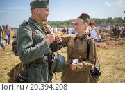 Купить «NELIDOVO, RUSSIA- JULY 12, 2014: Soviet soldier girl straightens uniform of a German soldier at the Battlefield 2014», фото № 20394208, снято 12 июля 2014 г. (c) Losevsky Pavel / Фотобанк Лори