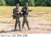 Купить «NELIDOVO, RUSSIA- JULY 12, 2014: Battlefield 2014: two Nazi soldiers go along the dusty road», фото № 20394348, снято 12 июля 2014 г. (c) Losevsky Pavel / Фотобанк Лори