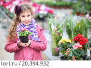 Купить «Smiling girl in a pink jacket holding flower pot in the hothouse», фото № 20394932, снято 1 марта 2014 г. (c) Losevsky Pavel / Фотобанк Лори