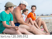 Купить «family of four sitting on pebbles», фото № 20395012, снято 19 июля 2014 г. (c) Losevsky Pavel / Фотобанк Лори