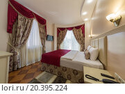Купить «ADLER, RUSSIA - JULY 22, 2014: Interior of a hotel room with drapes and high bed in Shine House hotel», фото № 20395224, снято 22 июля 2014 г. (c) Losevsky Pavel / Фотобанк Лори