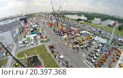 Купить «RUSSIA, MOSCOW - JUN 6, 2014: Visitors watch machines on territory of International Specialized Exhibition of Construction Equipment and Technologies 2014 at international exhibition center Crocus Expo. Aerial view. Photo with noise from action camera», фото № 20397368, снято 6 июня 2014 г. (c) Losevsky Pavel / Фотобанк Лори