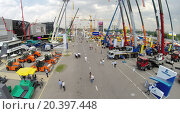 Купить «RUSSIA, MOSCOW - JUN 6, 2014: People walk near machines on International Specialized Exhibition of Construction Equipment and Technologies CET 2014 at international exhibition center Crocus Expo. Aerial view. Photo with noise from action camera», фото № 20397448, снято 6 июня 2014 г. (c) Losevsky Pavel / Фотобанк Лори