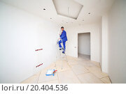 Купить «Man in blue on ladder pastes paint fiberglass in new apartment», фото № 20404536, снято 11 декабря 2013 г. (c) Losevsky Pavel / Фотобанк Лори