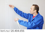 Купить «Worker in blue clothes works with painting fiberglass in new apartment», фото № 20404656, снято 11 декабря 2013 г. (c) Losevsky Pavel / Фотобанк Лори