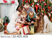 Family of five all together looks into gift box, sitting under Christmas tree. Стоковое фото, фотограф Losevsky Pavel / Фотобанк Лори