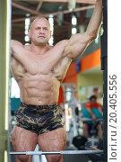 Купить «Handsome bodybuilder looks at mirror on his muscles in gym hall», фото № 20405556, снято 8 мая 2014 г. (c) Losevsky Pavel / Фотобанк Лори