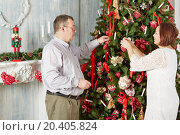 Купить «Man and woman decorate Christmas tree in room with fireplace», фото № 20405824, снято 26 декабря 2013 г. (c) Losevsky Pavel / Фотобанк Лори