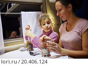 Купить «Young woman and her daughter sit in armchairs at coach department and prepare tea», фото № 20406124, снято 3 января 2014 г. (c) Losevsky Pavel / Фотобанк Лори