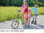 Купить «Mother and children ride bicycle and rollers on sunny day in park», фото № 20406260, снято 13 июля 2013 г. (c) Losevsky Pavel / Фотобанк Лори