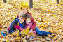 Mother with crown of yellow maple leaves on her head sits embracing her children in drift of fallen leaves, фото № 20406304, снято 13 октября 2013 г. (c) Losevsky Pavel / Фотобанк Лори