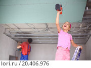 Купить «The girl with an electric screwdriver to fasten drywall on ceiling and man is working with a profile», фото № 20406976, снято 20 июля 2013 г. (c) Losevsky Pavel / Фотобанк Лори