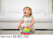 Купить «Cute little girl sits on carpet with toy and talks at home. Shallow depth of field.», фото № 20407232, снято 23 октября 2013 г. (c) Losevsky Pavel / Фотобанк Лори
